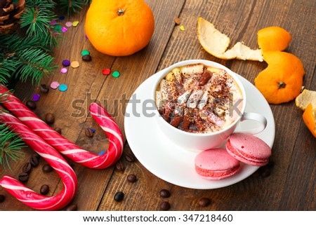 tangerines and fir-tree branches cone and Christmas candy and cookies and a Cup of coffee on wooden background