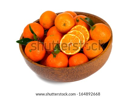 tangerines in a wooden bowl isolated on white