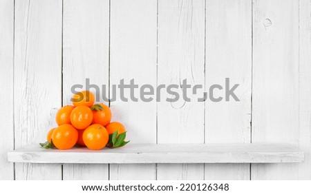 Tangerines on a wooden shelf. - stock photo