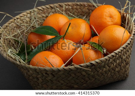 Tangerines with green leaves in a basket - stock photo
