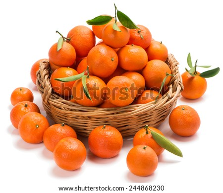tangerines with green leaves in a basket with some on the surface in the foreground isolated on white - stock photo