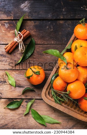 Tangerines with leaves and cinnamon stick on old wooden table. Top view. - stock photo