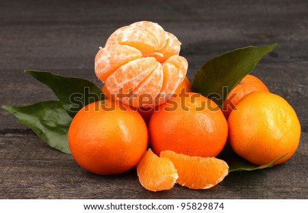 tangerines with leaves on wooden grey table - stock photo
