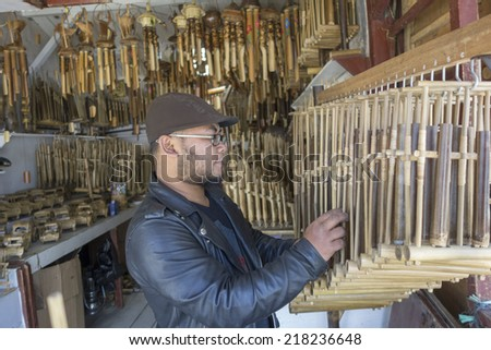 TANGKUBAN PERAHU, BANDUNG, WEST JAVA, INDONESIA - SEPTEMBER 15, 2014: Unidentified man plays traditional musical instrument, angklung, in Tangkuban Perahu, Indonesia. - stock photo