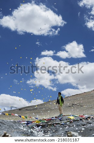 TANGLANG LA PASS, LADAKH REGION, INDIA - JULY 9, 2014: Young man scattering Buddhist prayer sheets at Tangangla pass July 2014 on the way to Leh for Kalachakra Buddhist festival