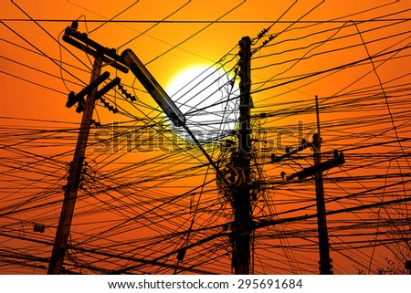 tangle cable and electricity post on sunset background