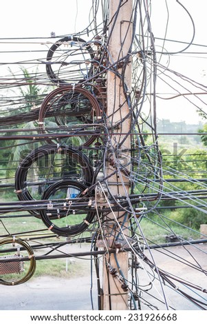 Tangle of cables and wires on pole - stock photo