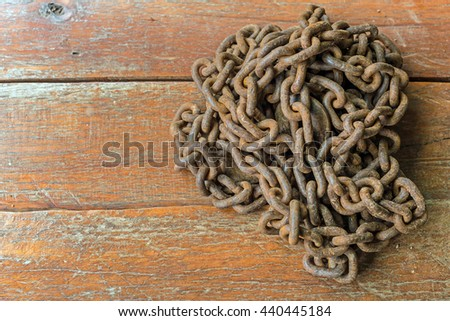 tangle of Rusty chains on wooden board with copy space - stock photo