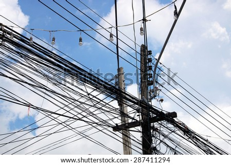 tangled web of cables connected to power supply on wooden pole