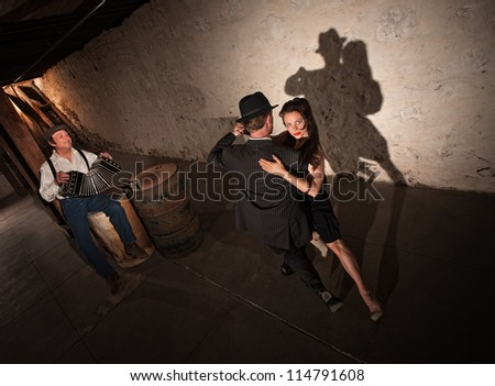 Tango dancers performing indoors with squeezebox player in background - stock photo