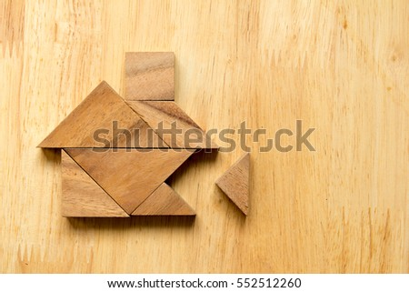 Tangram puzzle in home shape with the missing piece on wooden background (Concept for dream home)