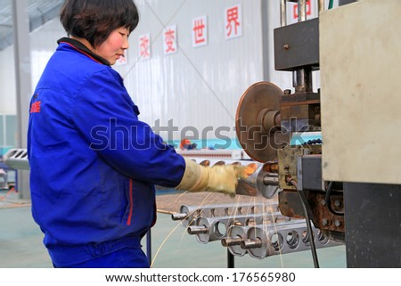 TANGSHAN, CHINA - DECEMBER 22: Worker in operating machinery on the production line, in a solar equipment production workshop on december 22, 2013, tangshan, china.