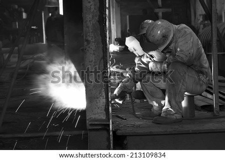 TANGSHAN CITY - JUNE 20: Worker welding parts in the production workshop, on June 20, 2014, Tangshan city, Hebei Province, China