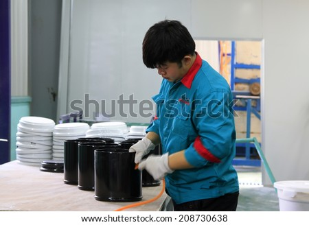 TANGSHAN CITY - MAY 29: Workers cleaning stainless steel drum enamel in a production workshop, on may 29, 2014, Tangshan city, Hebei Province, China