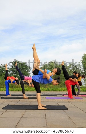 Tangshan - July 3: women doing yoga exercise in the park, July 3, 2016, tangshan city, hebei province, China