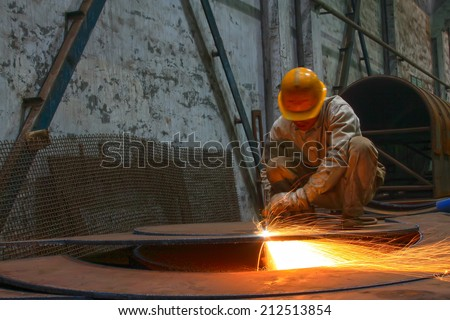TANGSHAN - JUNE 19: workers cutting the steel plate in the workshop, on June 19, 2014, Tangshan city, Hebei Province, China