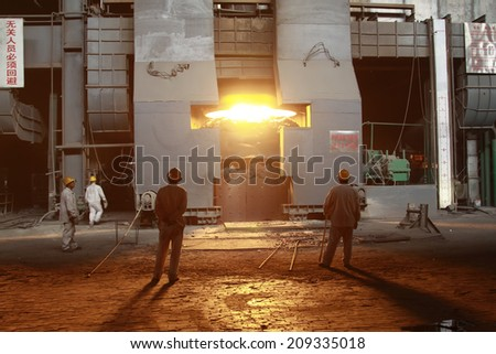 TANGSHAN - JUNE 14: Workers in front of the converter in iron and steel co., on June 14, 2014, Tangshan city, Hebei Province, China  - stock photo