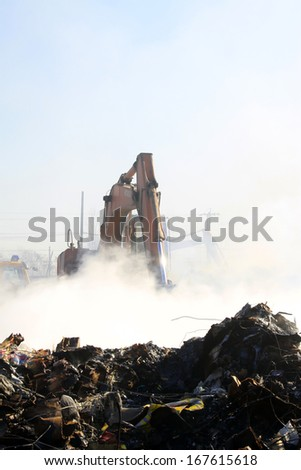 TANGSHAN - NOVEMBER 20: The excavators were clearing up rubbish after fire, November 20, 2013, tangshan city, hebei province, China.