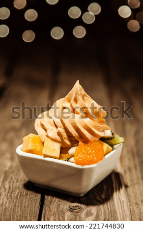 Tangy orange, mandarine or tangerine citrus frozen yogurt with fresh fruit salad in a owl on a rustic wooden table with copyspace and a bokeh of sparkling party lights - stock photo