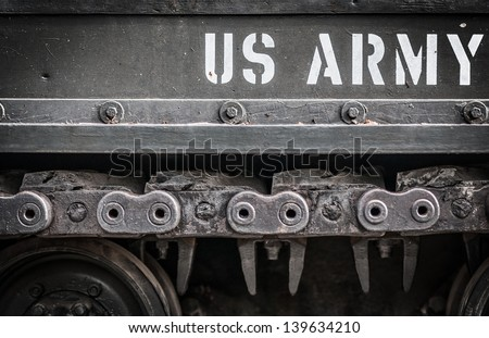 Tank close-up with wheel, caterpillar and text US Army on it. Focus on side of military transport with white letters outdoors. Armored machine of America. American tank. - stock photo