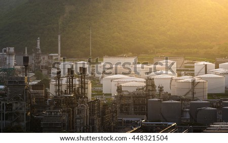 tank farm in oil refinery in front of the mountain and sun light in sunset time - stock photo
