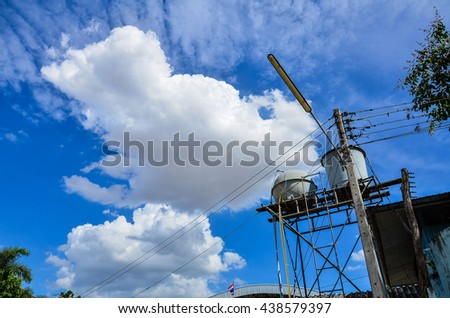 Tank for water supply and Lamp post at countryside looking at the bright sky and clouds .