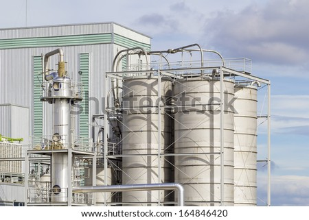 Tank of industrial process with blue sky background.
