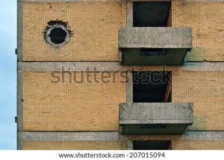 Tank shell impact on abandoned building brick wall - stock photo