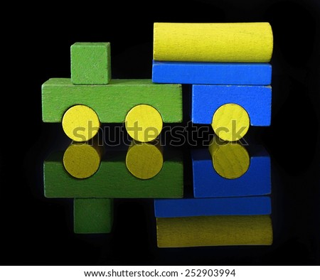 Tank truck of wooden blocks, traditional toy on black background - stock photo