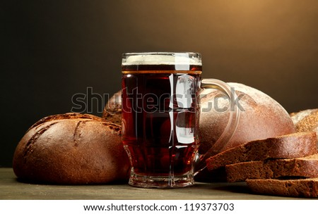 tankard of kvass and rye breads, on wooden table on brown background