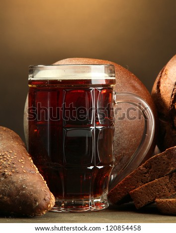 tankard of kvass and rye breads, on wooden table on brown background - stock photo