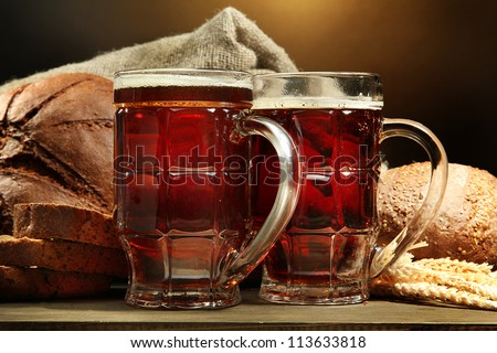 tankards of kvass and rye breads with ears, on wooden table on brown background - stock photo