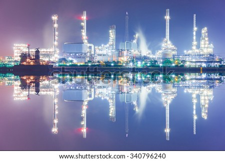 Tanker Oil Refinery with the boat parking near riverside in Night time. - stock photo