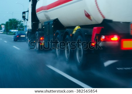 tanker on the move/tanker traveling on a wet road - stock photo
