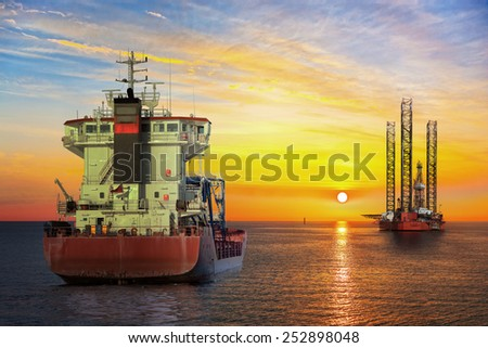Tanker ship and Oil Platform on offshore area at sunset. - stock photo