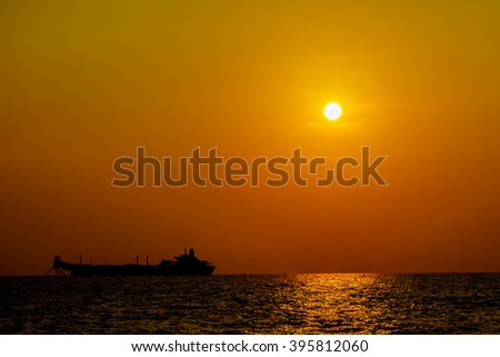 Tanker ship or supply boat in sunset for support oil and gas production of wellhead remote platform. Transfer oil and cargo for oil and gas industry, Energy and petroleum industry. - stock photo