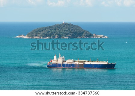 tanker ship sailing in the sea near an island - stock photo