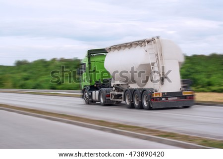 Tanker transporting fuel driving across the road motion blur natural environment