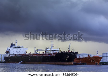 Tankers are moored at the jetty from a oil terminal. Violent disturbance in the air causing wind and clouds. - stock photo