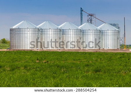 Tanks for the storage of grain standing in the field. The elevator in the background of green field. Granary for agricultural crops