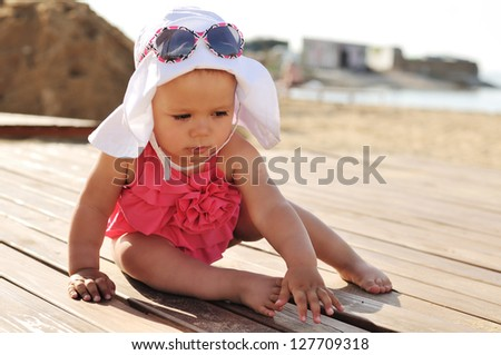 tanned baby girl on the beach - stock photo