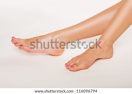 Tanned bare female feet with varnished toenails on a white background conceptual of podiatry, beauty, glamour , hygiene and body care - stock photo