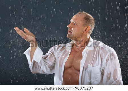 Tanned bodybuilder wearing white wet shirt stands in rain and catches drops by hand. - stock photo