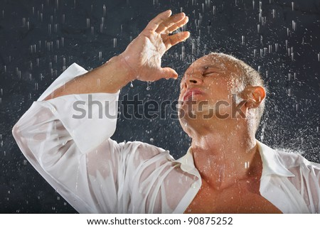 Tanned bodybuilder wearing white wet shirt stands in rain and closed hand from drops. - stock photo