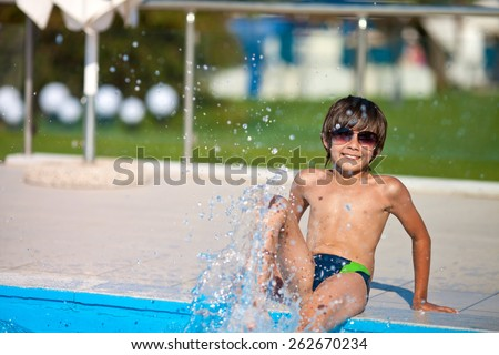 Tanned boy sitting and sprinkles the water in the pool summer day