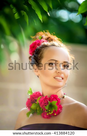 tanned girl in a tropical park, with make-up and decoration of flowers and fruits