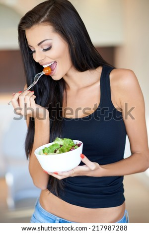 Tanned healthy young woman enjoying a mixed salad with fresh ingredients in a healthy lifestyle  fitness and diet concept - stock photo