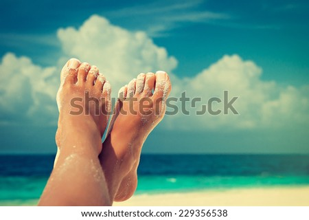 Tanned well-groomed feet amid tropical turquoise sea - stock photo