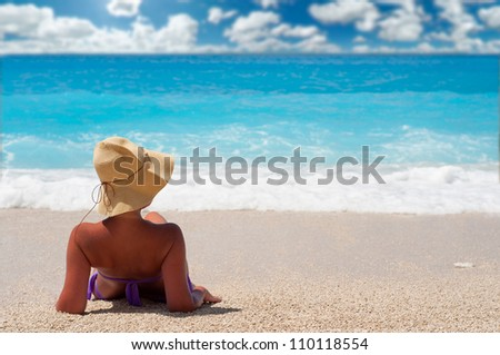 Tanned woman lying on the beach - stock photo