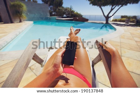 Tanned woman using smart phone by the poolside. Caucasian female model sunbathing on a deckchair and mobile phone. - stock photo
